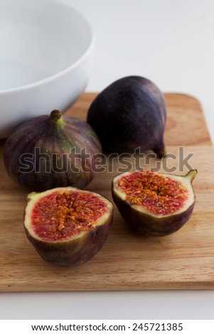 Ripe figs with ceramic bowl on the wooden board