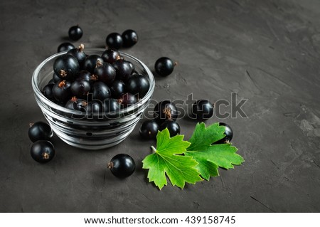 Ripe fresh black currants on dark background - stock photo