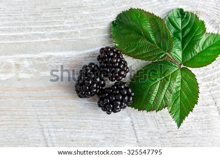 Ripe fresh blackberries on wooden background - stock photo