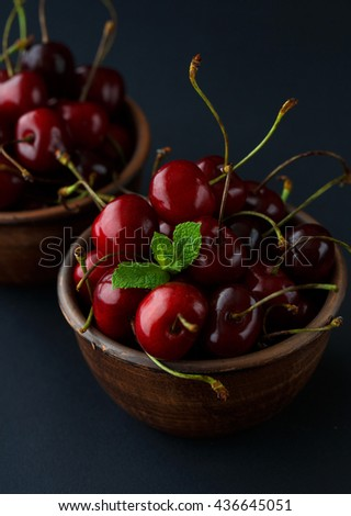 Ripe fresh cherries in a clay bowl on black background