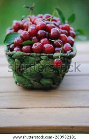 Ripe fresh cherries in a green wicker basket - stock photo