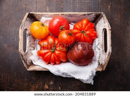 Ripe fresh colorful tomatoes in wooden box on dark wooden background - stock photo
