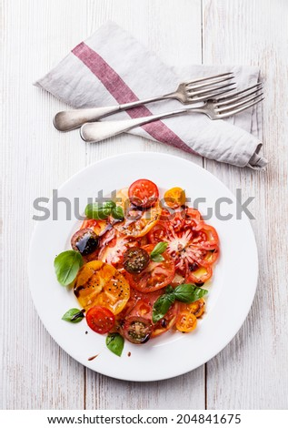 Ripe fresh colorful tomatoes salad with olive oil and balsamic vinegar on white wooden background - stock photo