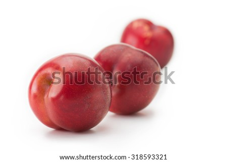 Ripe fresh harvested plums, isolated on white. Three red plums on white surface.?Focus on forehand plum.