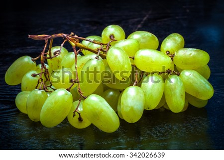 Ripe fresh juicy grape on a black table or board like background. Toned. - stock photo