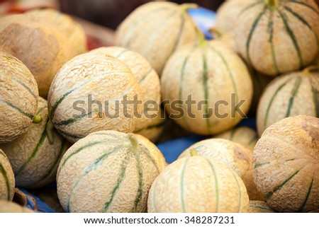 Ripe fresh melons pile in a farmers market. Horizontal shot