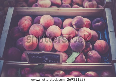 Ripe fresh peaches in a french farmers market. Horizontal filtered shot with a selective focus - stock photo