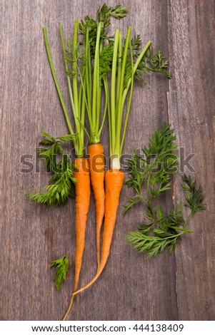 ripe fresh raw carrot with leaf on wooden background - stock photo
