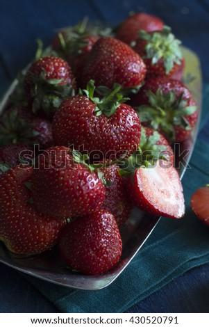 Ripe fresh strawberries on metal plate. Dark photo - stock photo