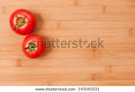 Ripe fresh tasty tomatoes on a wooden cutting board, with copy space.