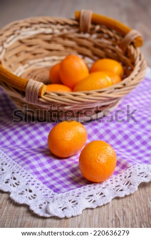 Ripe fruit kumquat orange lying on a wooden surface against the background of a wicker basket