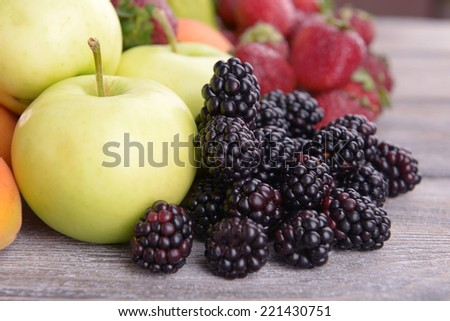 Ripe fruits and berries on wooden background - stock photo