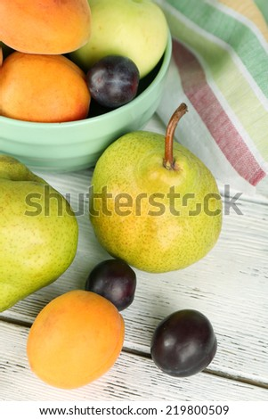 Ripe fruits in bowl on table close up