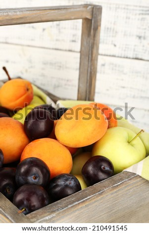 Ripe fruits in crate on wooden background