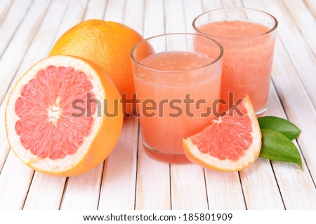 Ripe grapefruit with juice on table close-up - stock photo