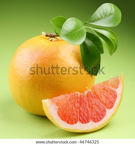 Ripe grapefruit with segment on a green background - stock photo