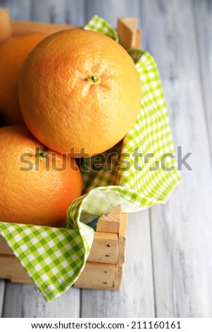 Ripe grapefruits in wooden box  on wooden background - stock photo