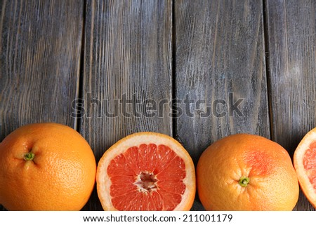 Ripe grapefruits on wooden background - stock photo