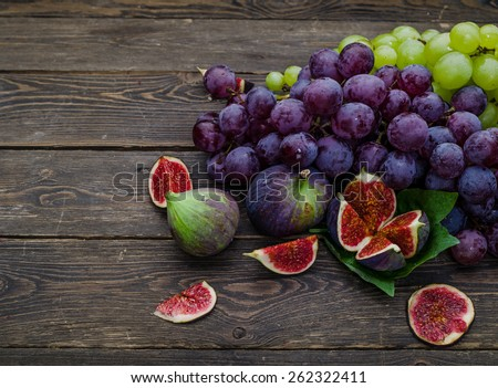Ripe Grapes and Figs on dark wooden table - stock photo