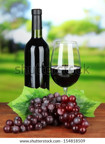 Ripe grapes, bottle and glass of wine on bright background - stock photo