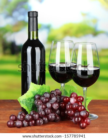 Ripe grapes, bottle and glasses of wine on bright background