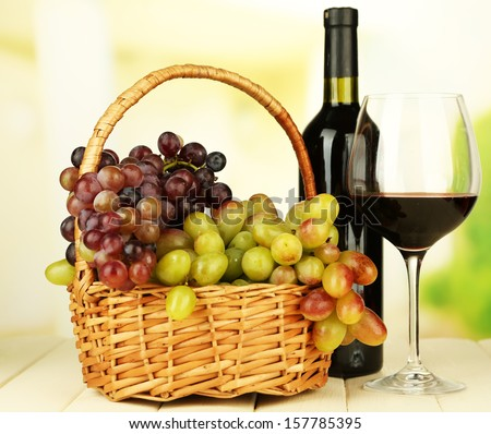 Ripe grapes in wicker basket, bottle and glass of wine, on light background