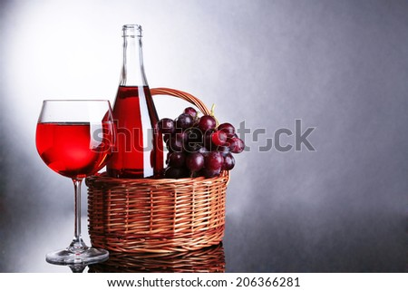 Ripe grapes, wine glass and bottle of wine on grey background - stock photo