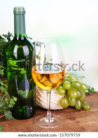 Ripe green and purple grapes in basket with wine on wooden table on bright background