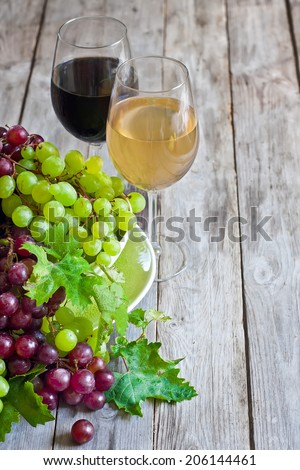 Ripe green and red grape and white and red wine in goblets. Copy space background. - stock photo