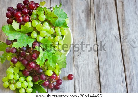 Ripe green and red grape in ceramic bowl. Copy space background. - stock photo