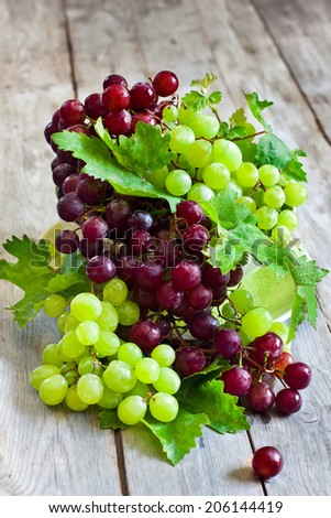 Ripe green and red grape in ceramic bowl. Selective focus. - stock photo