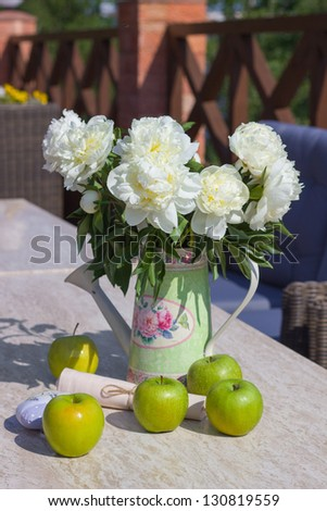 ripe green apples and a vase of peonies on a marble table - stock photo