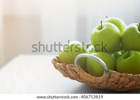 Ripe green apples in a wicker basket on a kitchen table - stock photo