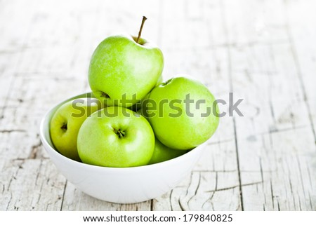 ripe green apples in bowl on wooden background - stock photo