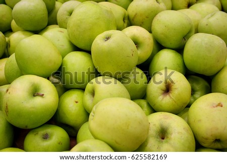 Ripe green apples lie on top of each other