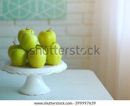 Ripe green apples on a stand in kitchen - stock photo