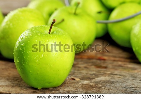 Ripe green apples on wooden table close up - stock photo