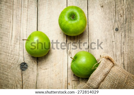 Ripe green apples with burlap, on wooden  background - stock photo