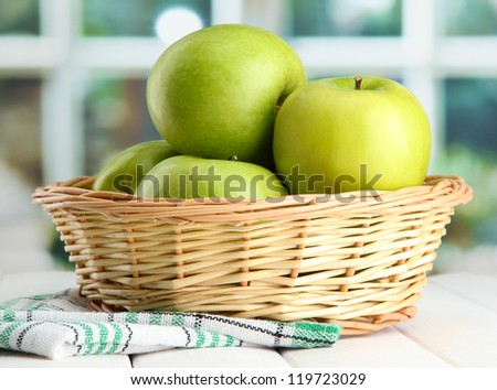 Ripe green apples with leaves in basket, on wooden table, on window background - stock photo