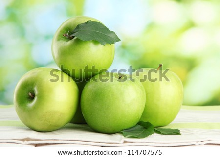 Ripe green apples with leaves, on table, on green background - stock photo