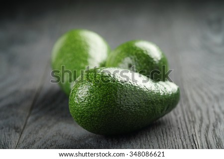 ripe green avocados on wood table, selective focus