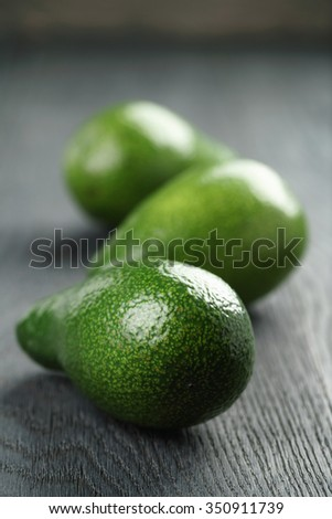 ripe green avocados on wood table, selective focus - stock photo