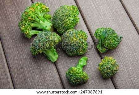 Ripe green broccoli cabbage on wooden background - stock photo
