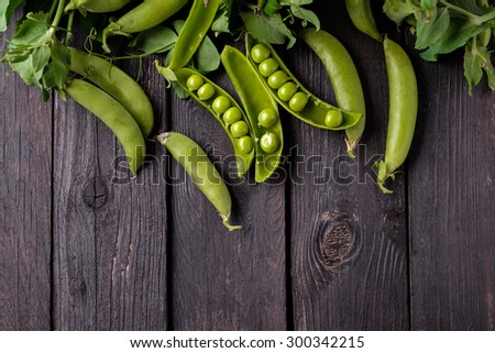 Ripe Green peas on wooden table - stock photo