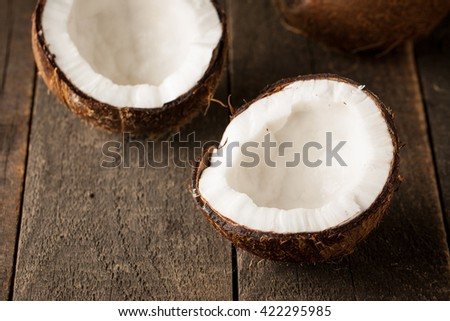 Ripe half cut coconut on a wooden background. - stock photo