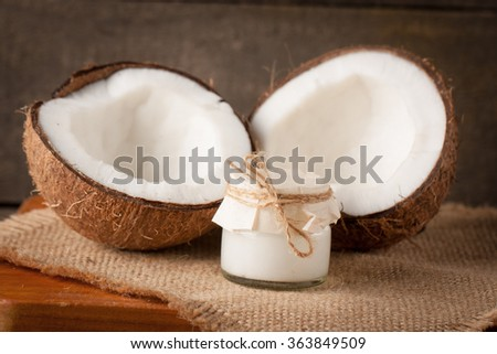 Ripe half cut coconut on a wooden background. Ripe half cut coconut on a wooden background. Coconut cream and oil. - stock photo