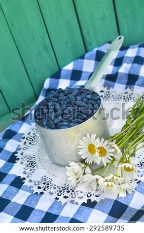 Ripe honeysuckle berry in old ladle with bunch of daisy flowers on white napkin, vintage still life - stock photo
