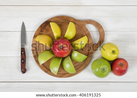 Ripe juicy apples lie on wooden board with a knife next to it in top view - stock photo