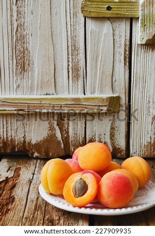 ripe juicy apricots in a plate on old wooden table.health and diet food. copy space for text - stock photo