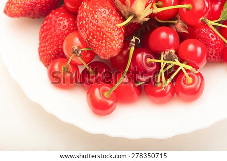 ripe juicy cherries and berry in plates on the table - stock photo